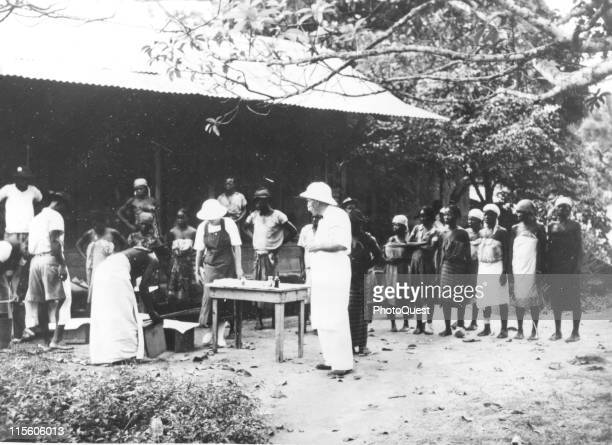 Germanborn French medical missionary and theologian Dr Albert Schweitzer stands with his patients at an openair clinic near his home Lambarene Gabon...