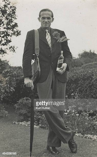 German-born photographer Kurt Hutton leaning on an umbrella and holding a bottle of whisky in the garden of his home in Hampstead Garden Suburb,...