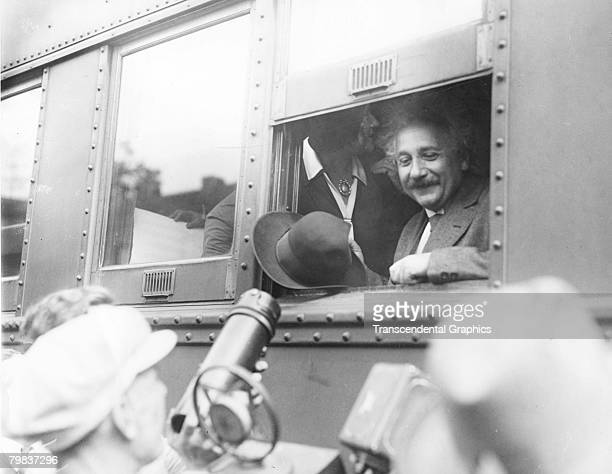 Germanborn physicist Dr Albert Einstein smiles at supportors and newsmen out of the window of a train Chicago Illinois early 1930s His wife Elsa...