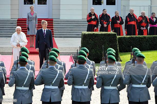 German-born Pope Benedict XVI , German President Christian Wulff and his wife Bettina Wulff stand in front of soldiers at the Bellevue Palace on...
