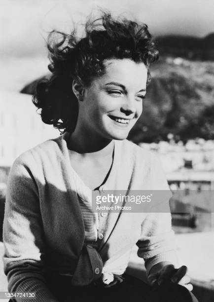 German-French actress Romy Schneider , wearing an unbuttoned cardigan, smiling as the wind blows her hair back, in an unspecified publicity portrait,...