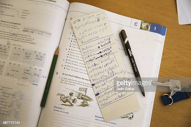 Germanlanguage exercise book and a slip of paper with notes in Arabic lie on the table of a migrant from Syria who is trying to learn German in his...