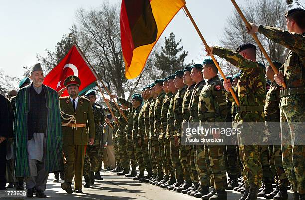 German-Netherlands and Turkish International Security Assistance Force soldiers stand at attention as Afghan President Hamid Karzai arrives for the...