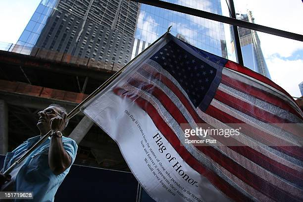 Germano Riviera walks with the 'Flag of Honor' which displays the names of all of the victims of the September 11 terrorist attacks across from...