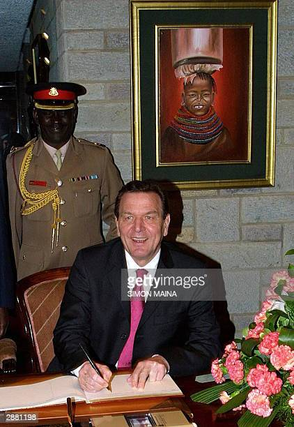 German's Chancellor Gerhard Schroeder signs a visitors book after arriving at the Jommo Kenyatta International Airport 19 January 2004 for a two day...