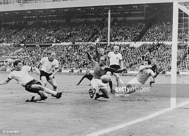 Germans score twice...Wolfgang Weber of West Germany scores his team's second goal as England's Ray Wilson and goalie Gordon Banks try to stop ball...