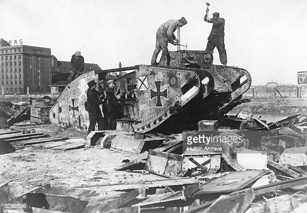 Germans take war machines apart outside Berlin Under the terms of the Treaty of Versailles Germany was required to disarm This tank is in fact a...