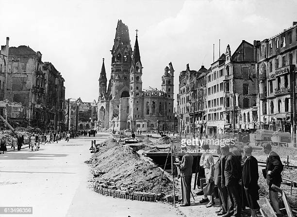 Germans watch an artist painting the battlescarred streets of Berlin including the Kaiser Wilhelm Memorial Church in Tauenzien Strasse   Location...