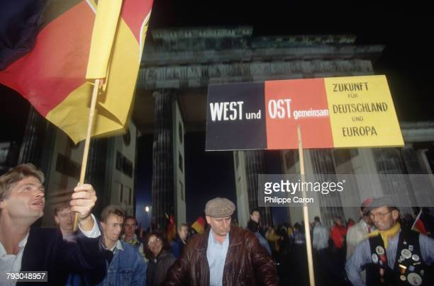 Germans wave flags and signs in front of Brandenburg Gate as they celebrate the reunification of East and West Germany The previous day on October 2...