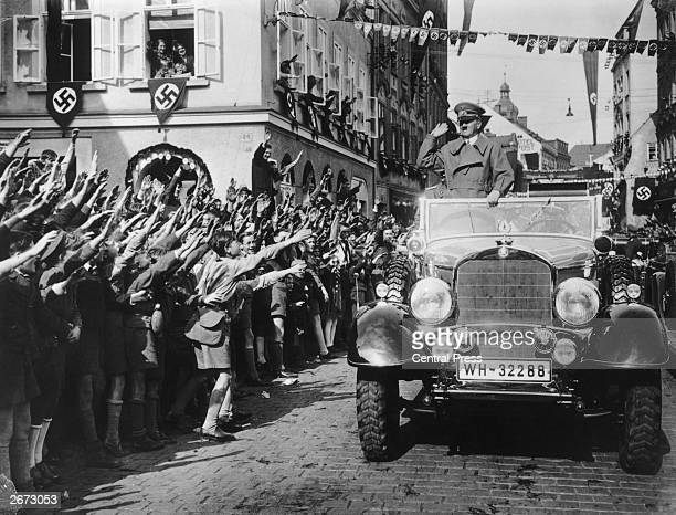 Germanspeaking schoolchildren welcome German dictator Adolf Hitler in a street decorated with swastikas in the Sudetenland Czechoslovakia The...
