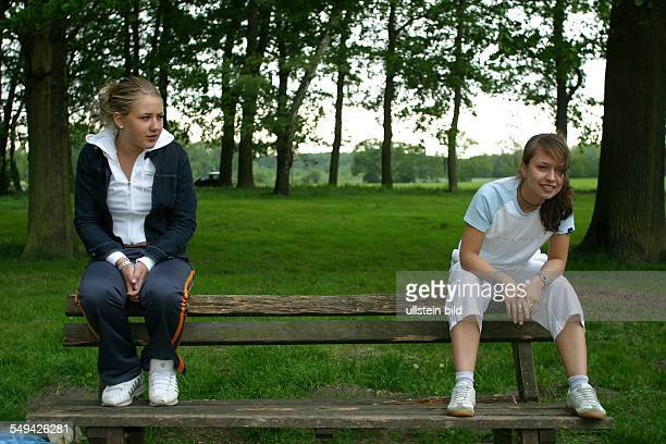 Free time Two women sitting in great distance next to each other on the backrest of an old wooden bench
