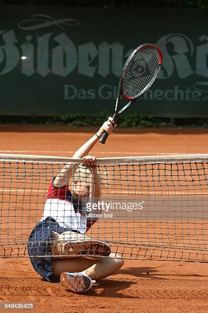 A young woman on a tennis court she is slipped