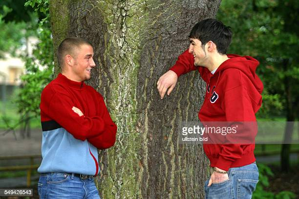Portrait of two young persons they are leaning against a tree talking