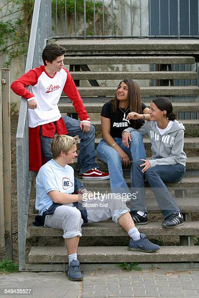 Free time Four young persons sitting on a staircase talking