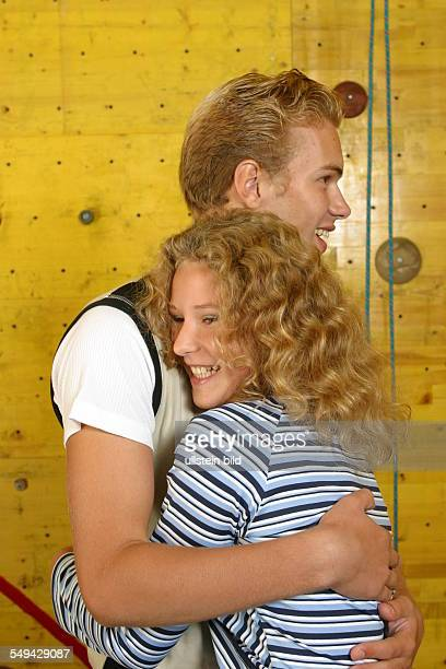 Free time/sport A girl and a boy in front of a climbing wall they embrace each other