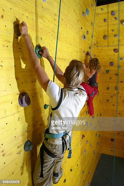 Germany, : Free time/sport.- Two young persons climbing up a climbing wall.