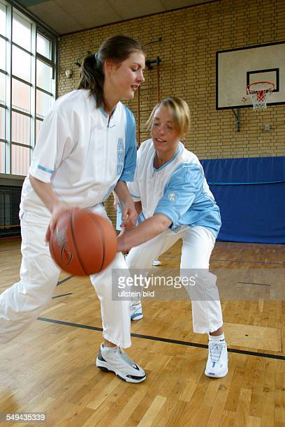 Germany, : Free time/sport.- During a basketball match in a gymnasium; duel between two young women.