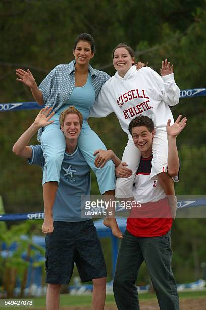 Holidays Four youth on a beach volleyball field the girls sitting on the boy s shoulders