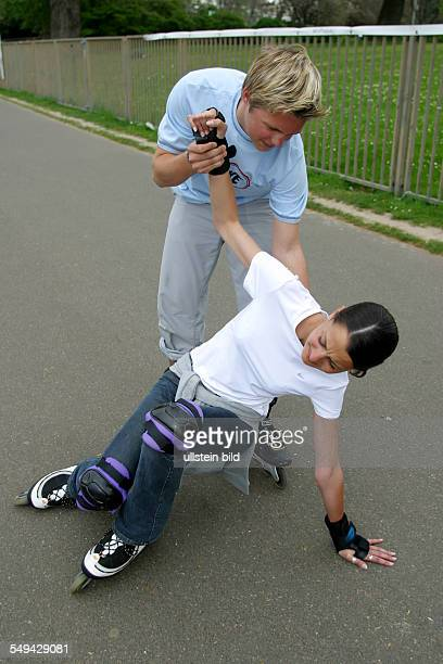 Free time A girl falled with her inline skates a boy is helping her to stand up
