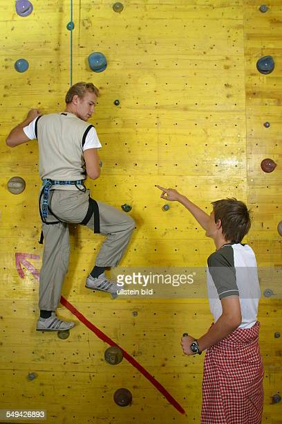 Free time/sport A boy is climbing up a climbing wall while another boy is giving him instructions