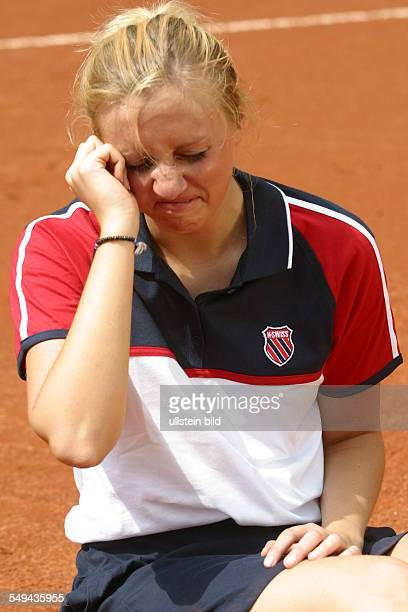 Germany, : Portrait of a young woman on a tennis court.- She is sitting on the court crying.
