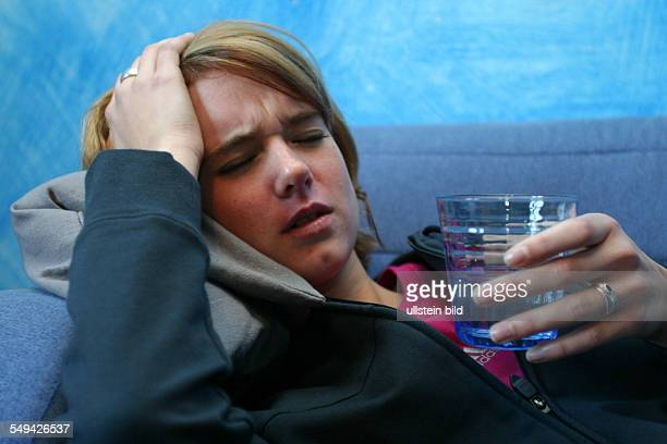 Free time Portrait of a young woman she is lieing on a sofa with a glass of water in her hand She is holding her aching head