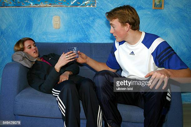 Free time A girl lieing on a sofa while a boy is serving her a glass of water