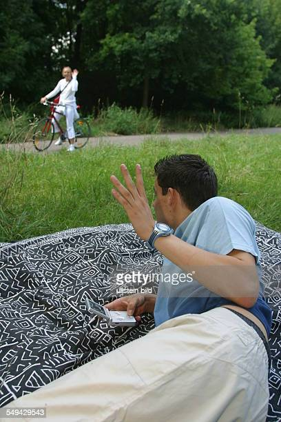 A young man lieing with his blanket on a meadow playing gameboy He is waving to a young woman who is riding past