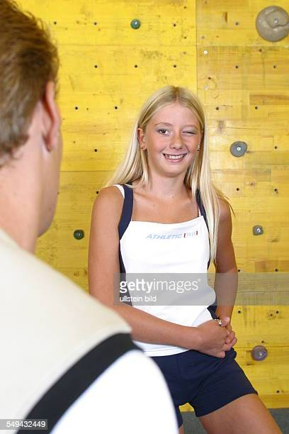 Free time/sport In front of a climbing wall a girl is winking to a boy who is standing opposite her