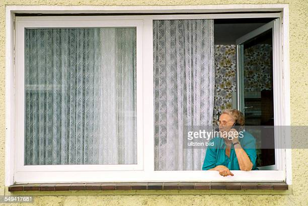 Germany, 1998: Communication; a senior citizen with a mobile phone at the window.