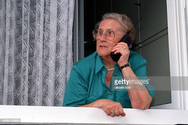 Communication media senior citizen calls with a cellular phone at the window