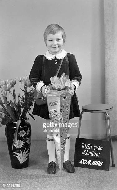A girl stands between a vase and a stool at her first school day She holds a paper funnel in front of herself