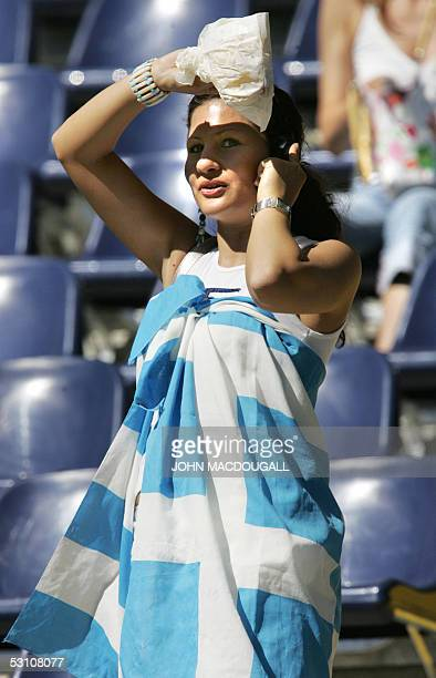 Germany: A Greek supporter wrapped in her national flag speaks on her cellphone at the beginning of the 2005 FIFA Confederations Cup football match...