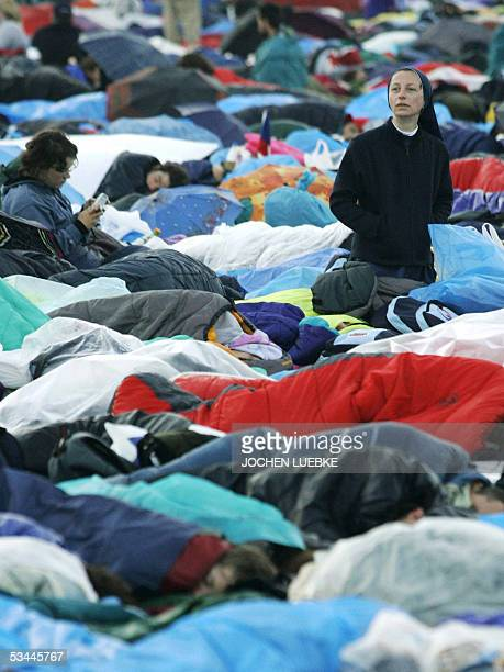 Nun wakes up as other pilgrims are sleeping at the Marienfeld, early 21 August 2005 near Kerpen, on the last day of the World Youth Day festival and...
