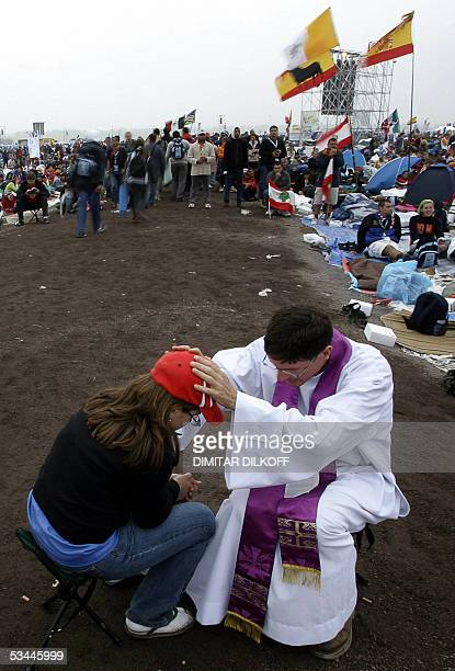 Priest hears a confession prior to attending Pope Benedict XVI's Sunday mass at Marienfeld in Kerpen, a park on the former site of a coalmine near...