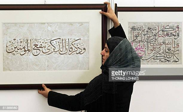 A Publisher's associate hangs up a calligraphy by artist Sami AlGawy of Oman in the Arab Pavillion 04 October 2004 ahead of the 56th edition of the...