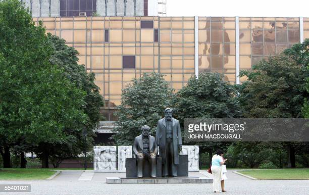 Statue of Karl Marx and Friedrich Engels, the main theoreticians of Communism, stands in front of the Palace of the Republic, the historic building...