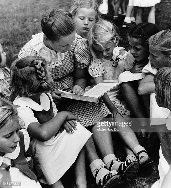 Germany : A student of the School of Arts and Crafts in Stuttgart reading to children of a kindergarten run by Nazi Germany's women's association -...