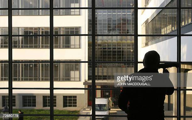 A worker cleans a window in one of the wings of the Bauhaus building in Dessau 30 November 2006 The building which housed the Bauhaus design school...