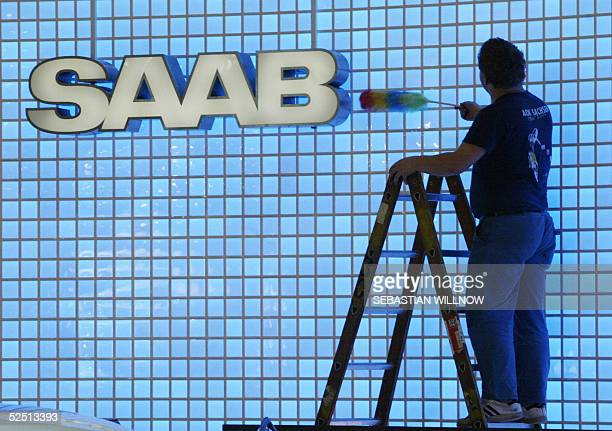 A worker cleans the logo of Swedish car maker Saab 31 March 2005 at the fair grounds in Leipzig in preparation of the Auto Mobil International fair...