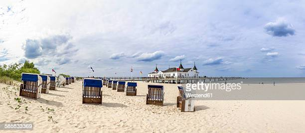 Germany, Ahlbeck, view to sea bridge with hooded beach chairs on the beach in the foreground