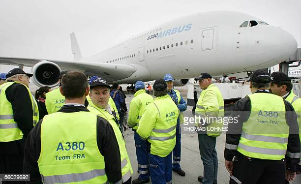 Airport employees stand in front of the new superjumbo Airbus the A380 that landed early 29 October 2005 at Frankfurt am Main airport on its first...