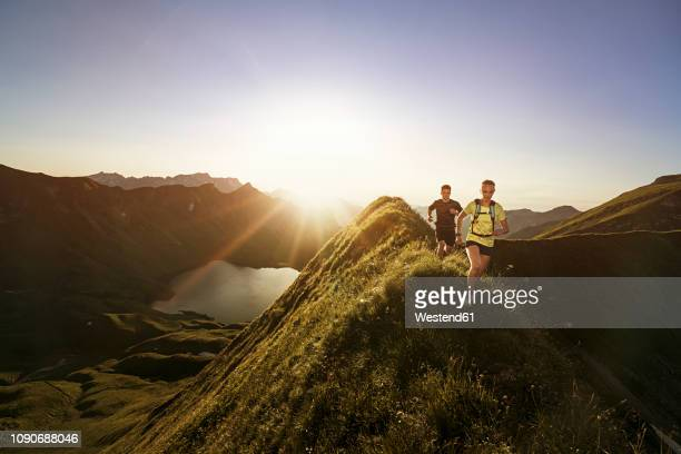 germany, allgaeu alps, man and woman running on mountain ridge - passion stock pictures, royalty-free photos & images