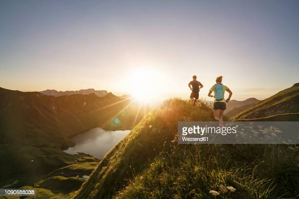 germany, allgaeu alps, man and woman running on mountain trail - vitality stock-fotos und bilder