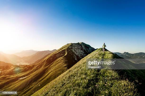 germany, allgaeu alps, woman running on mountain ridge - berg stock-fotos und bilder