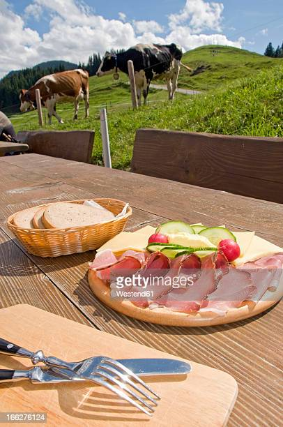 Germany, Allgau, Torggelen, Solid snack on table, cattle in background