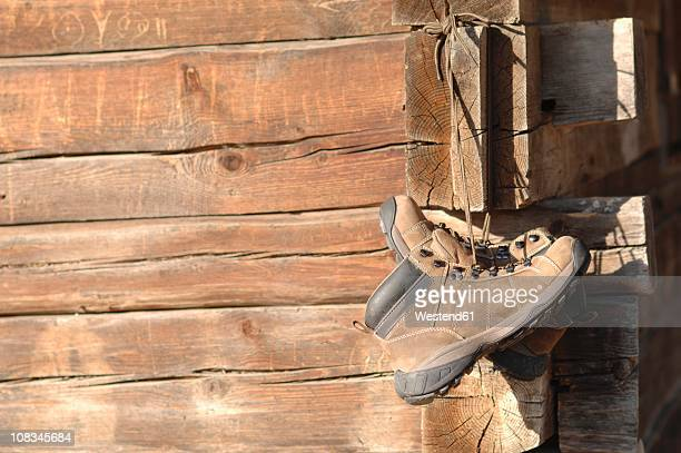 Germany, Ammersee, Hiking shoes hanging on wood lodge