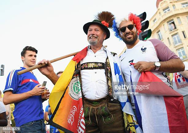 Germany and France supporters enjoy the atmosphere with police officers prior to the UEFA EURO semi final match between Germany and France at Stade...