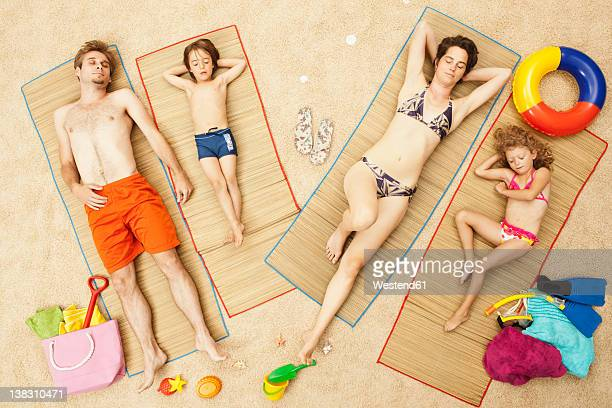Germany, Artificial beach scene with family lying on mat