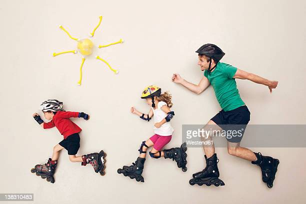 germany, artificial scene with family doing inline skating - inline skate stock photos and pictures